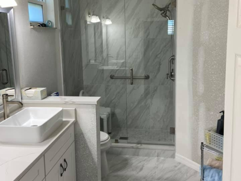 remodeled bathroom with white vessel sinks and glass shower